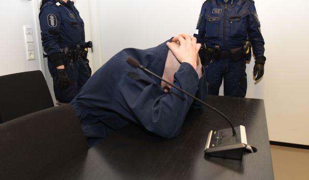 Mieskolmikko vangittiin viime viikon perjantaina Länsi-Uudenmaan käräjäoikeudessa Espoossa epäiltynä lohjalaismiehen murhasta. 25-vuotias epäilty peitti oikeussalissa päänsä ja kasvonsa.