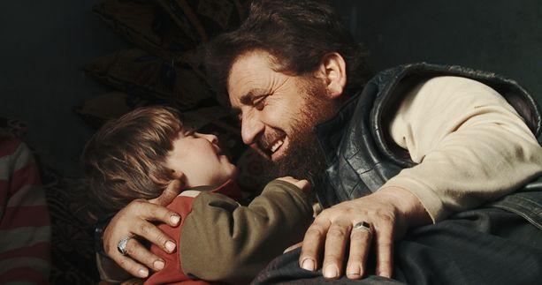 Abu Osama leikkii yhden nuoremman lapsensa kanssa kotonaan Syyrian Idlibissä.