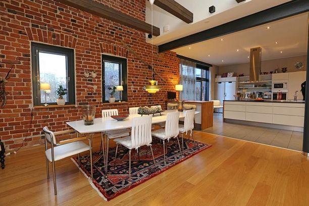 Vanhaan puolustusvoimien rakennukseen tehdyn loft-asunnon keittiössä ja ruokailutilassa on perinteinen punatiilinen seinä ja tummat kattoparrut.