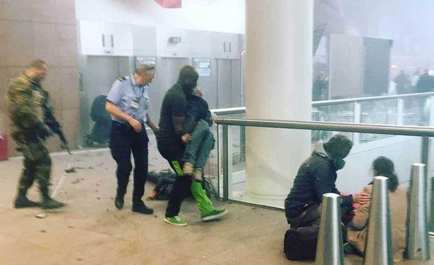Ihmiset auttoivat toisiaan lentokentällä. Loukkaantuneita kannettiin turvaan.