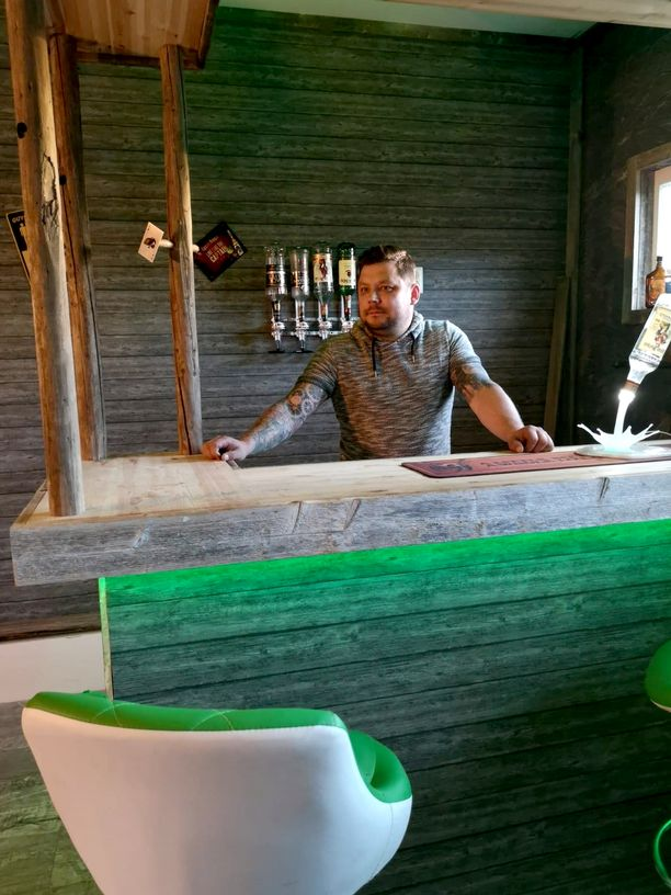 Janne Kokkonen baaritiskin takana. Komeat värivalot ja valkovihreät baarijakkarat on mietitty yks yhteen.