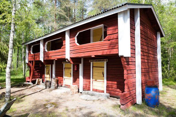 Tapion Tuvan pihapiirissä on vanhoja hirsirakennuksia. Aitoissa voi myös majoittua.