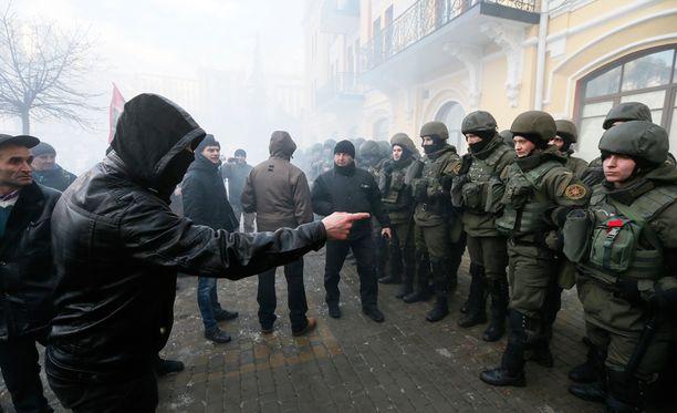 Kuvassa mielenosoittajat soittavat suutaan Ukrainan poliisille sunnuntaina Kiovassa.