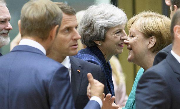 Donald Tusk ilmoitti varhain aamulla, että sopu on saavutettu. Oikealla puolella Theresa May ja Angela Merkel.