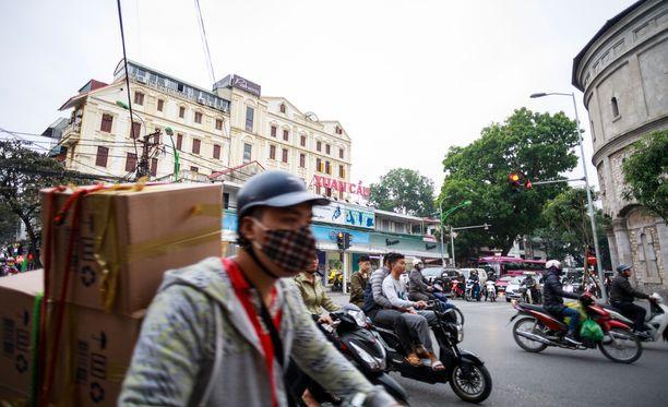 Hengityssuojaan naamioituneet mopoilijat ovat Hanoissa tuttu näky.