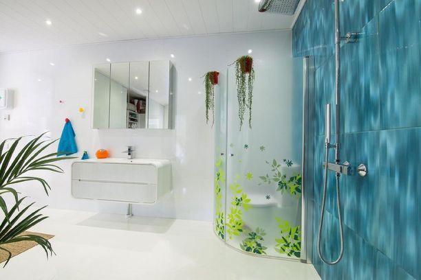 Valkoista kylpyhuonetta koristaa sinisillä laatoilla toteutettu tehosteseinä.
