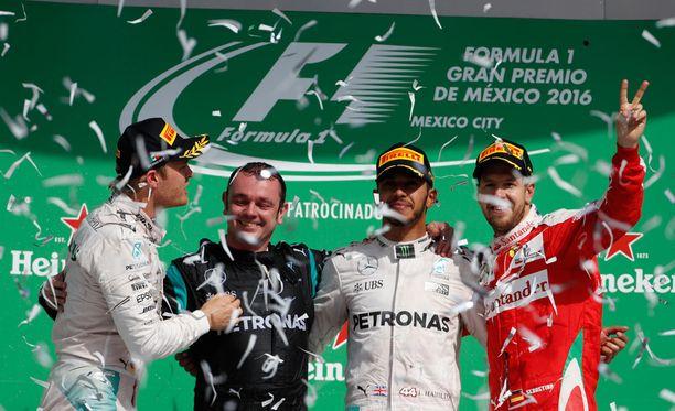 Nico Rosberg, Mercedeksen henkilöstöön kuuluva Tony Walton, Lewis Hamilton ja Sebastian Vettel kinkeröivät palkintopallilla.