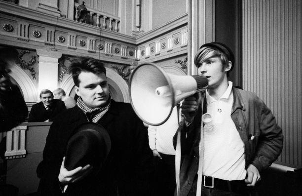 Helsingin yliopiston ylioppilaskunnan 100-vuotisjuhlatilaisuuksien aattona, 25. marraskuuta 1968 opiskelijat valtasivat Vanhan ylioppilastalon. Valtaajien tavoitteena oli herättää kriittistä keskustelua Helsingin yliopiston ylioppilaskunnasta sekä itse yliopistosta. Päämääränä oli yliopistodemokratian lisääminen. Oikealla Erkki Tuomioja megafoni kädessä ja vasemmalla SYL:n hallituksen edustaja Jyrki Vesikansa.