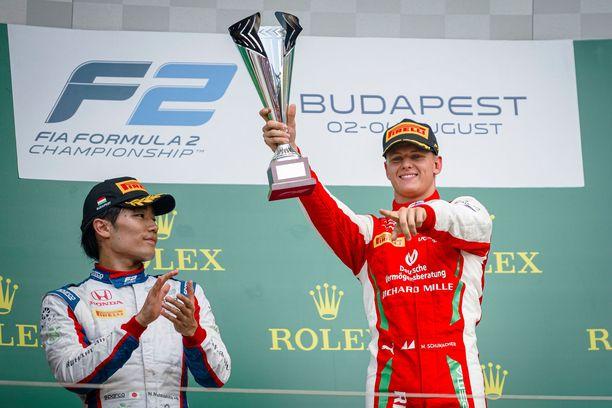 Prema Racing's German racing driver Mick Schumacher (R) celebrates on podium after winning the second race
