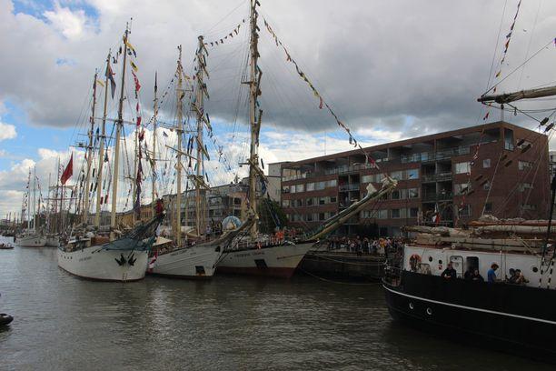 Osa suurista purjelaivoista on ankkuroitu vierekkäin joen rantaan.