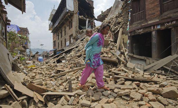 Nainen kantaa vauvaa selässään talojen raunioissa Kathmandussa.