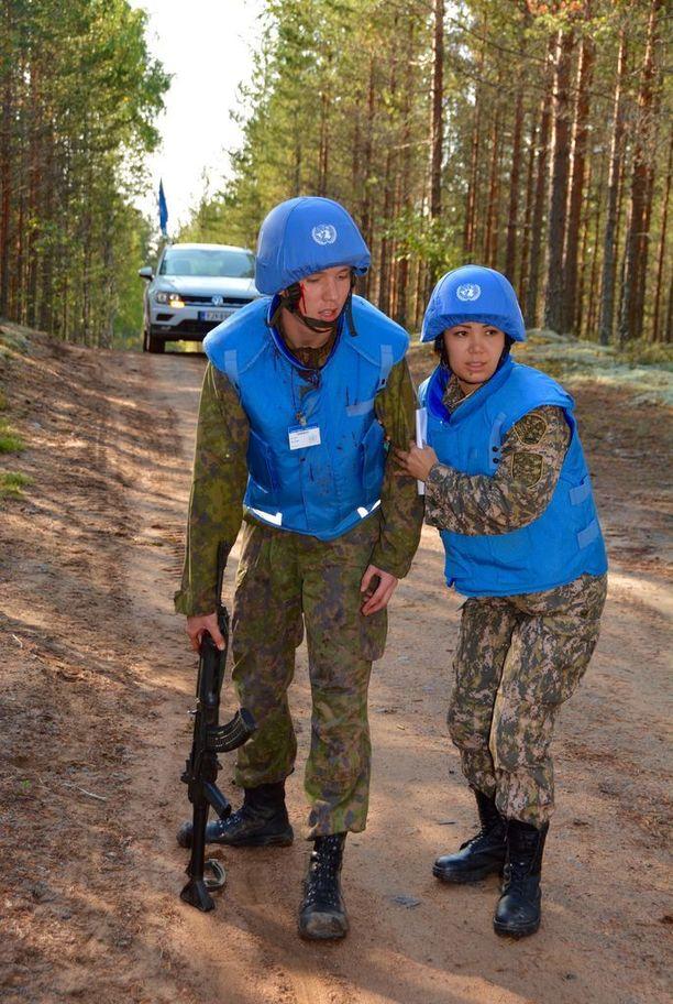 Kasakstanilainen luutnantti Aizhan Zhassuzakova auttaa miinaonnettomuudessa haavoittunutta rauhanturvaajaa näyttelevää, Porin Prikaatissa varusmiespalvelustaan suorittavaa Leevi Koskenniemeä. (Asko Tanhuanpää)