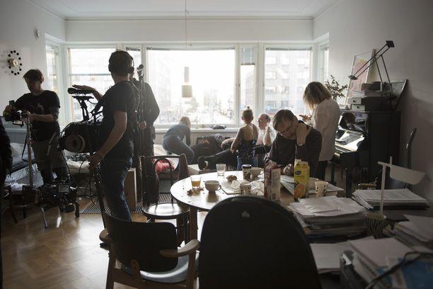 Töölöläisasunto on lavastettu Hannu-Pekka Björkmanin esittämän Pekka Malmikunnaksen kodiksi. Asko Sarkola perehtyy pöydän ääressä vuorosanoihinsa kuvausryhmän valmistellessa seuraavaa ottoa.