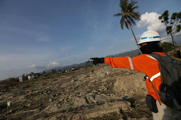 Pelastustyöntekijä Petobon kylässä, jonka mutavyöry tuhosi. Taustalla näkyvillä valkoisilla lipuilla merkataa mudan alla olevia ruumiita.