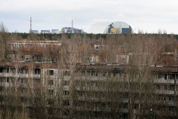 Pripjatin kaupungin talot pysyvät hylättyinä. Tshernobylin piiput näkyvät taustalla.