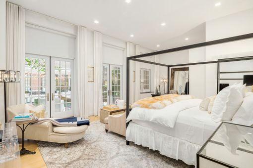 Yksi asunnon neljästä makuuhuoneesta. Huonetta hallitsee moderni pylvässänky.