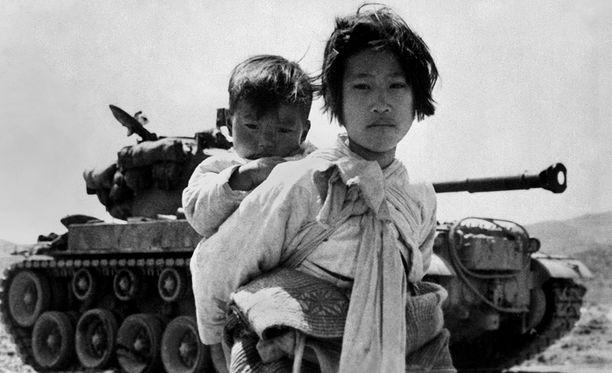 Sisko kantaa veljeään turvaan, taustalla M26-tankki. Kuva on otettu kesäkuussa 1951.