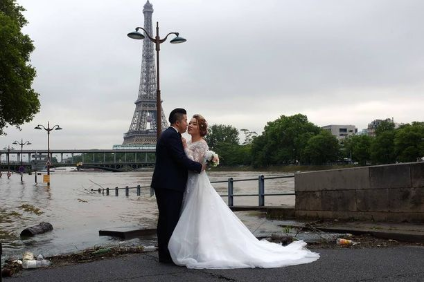 Kiinalaispari otti hääkuvan Eiffel-tornin edustalla Pariisin tulviessa.