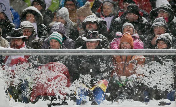Katsojat värjöttelivät lumisateessa.