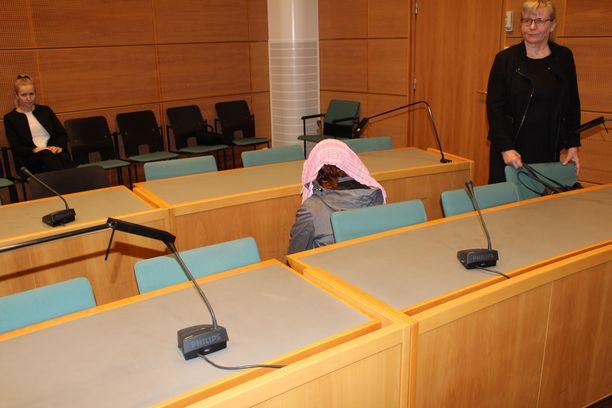Syytteen saanut äiti peitti kasvonsa kameroilta oikeudessa.