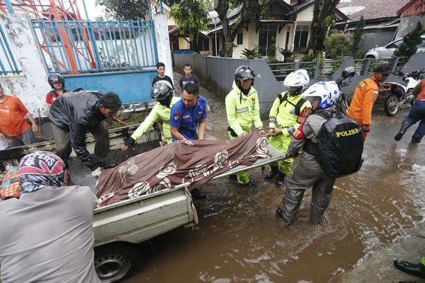 Pelastustyöntekijät siirtävät ruumiit pois tuhoalueelta.