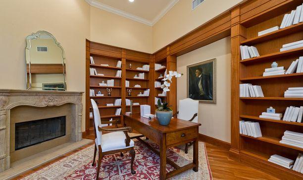 Kodissa on kiinteät kirjahyllyt ja tumma parkettilattia.
