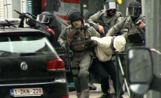 Poliisin iskujoukot vangitsemassa epäiltyä Brysselissä tehdyssä ratsiassa, jossa saatiin kiinni Pariisin iskujen pääsuunnittelija Salah Abdeslam.