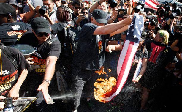 Poliisi yrittää sammuttaa palamaan sytytetyn lipun mielenosoittajien vastustellessa.