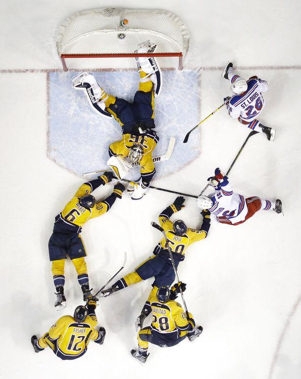 KAAOS Pekka Rinne ja Nashville Predatorsin puolustus selvisivät New York Rangersin hyökkäyksestä. Kiekko on Rinteen alla.