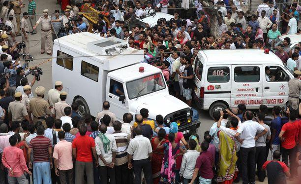 Ambulanssit kuljettavat pois ruumiita.