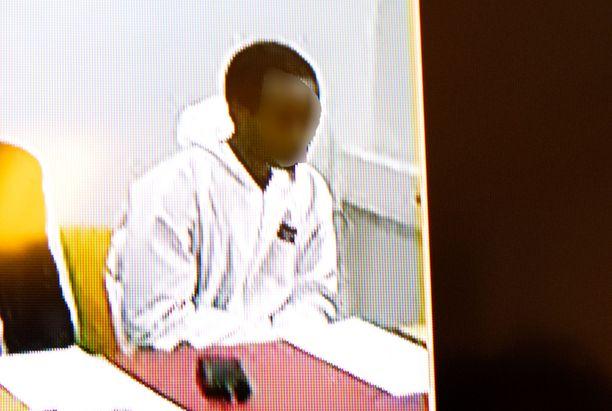 Nuori mies tuodaan oikeuden eteen Oulussa. Kuva vangitsemisistunnosta.