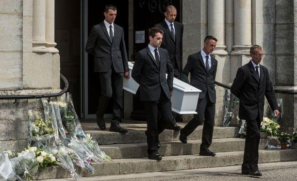 Arkunkantajat kirkon ovella. Vainaja laskettiin haudan lepoon kotikylässään.