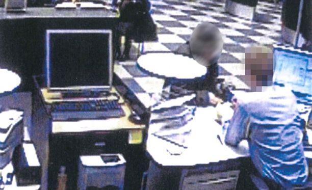 Valvontakameran kuvasta näkyy, kuinka taustalla istuva nainen seuraa, kun yli 80-vuotias nainen asioi pankkitiskillä.