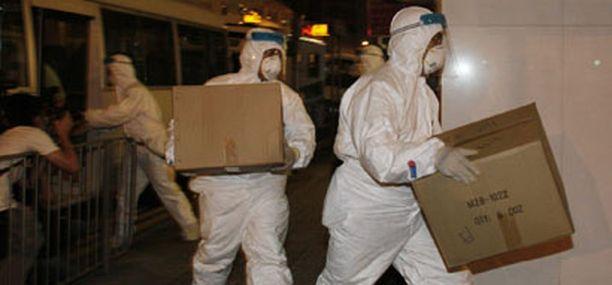 Sairaanhoitohenkilökunta marssi hotellin suoja-asuissaan.