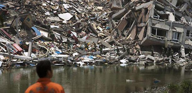 Pelastustyöntekijä tarkastelee sortuneen talon raunioissa kulkevia sotilaita Beichuanissa.