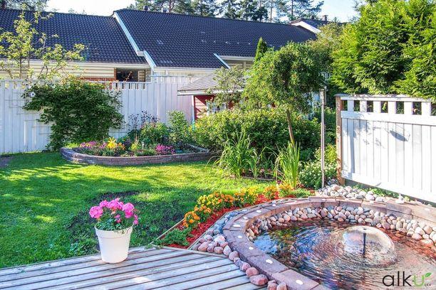 Kun tilaa on hieman enemmän, voi saada molemmat: pihan nurmikkoineen ja terassin löhöilykalusteineen. Tällä pihalla on satsattu kauniisiin istutuksiin ja suihkulähteeseen. Pieni terassi tarjoaa tilan pihakalusteille ja grillille.