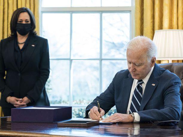 Yhdysvaltain presidentti Joe Biden allekirjoitti massiivisen elvytyspakettinsa etuajassa torstaina varapresidentti Kamala Harrisin seuratessa sivusta.