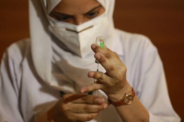 Intialainen terveydenhoitotyöntekijä annostelemassa Serum-instituutin valmistamaa Astra Zenecan rokotetta. Karu koronatilanne voi aiheuttaa viivästyksiä Intiassa valmistettavien lääkkeiden ja rokotteiden tuotantoon.
