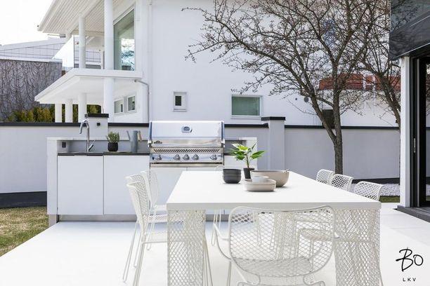 Tämä supermoderni kesäkeittiö näyttää siltä kuin keittiö olisi tuota sisältä ulos. Valkoiset pinnat vaativat huolenpitoa.