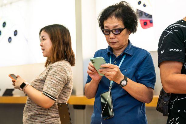 Naisasiakas tutkii iPhone 11 -mallia Shanghaissa. (Kuvituskuva)
