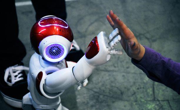 Aurinkolahden koulun Tuisku-robotti lyö kättä oppilaiden kanssa.
