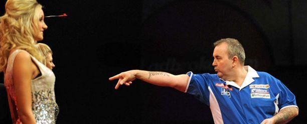 Phil Taylor (oik.) viihdytti MM-kisojen yleisöä heittämällä tikkoja naisen ohi otteluiden välillä.