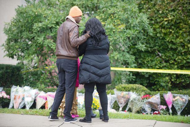 Ihmiset veivät kukkia uhrien muistoksi synagogan lähettyville Pittsburghissa sunnuntaina.