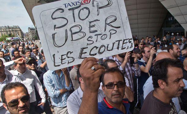"""Taksinkuljettaja pitää Pariisissa järjestetyssä mielenosoituksessa kylttiä, jossa lukee: """"Lopeta Uber, lopeta kuunteleminen."""""""