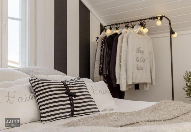Mustavalkoinen sisustus makuuhuoneessa näyttää raikkaalta. Hauskan lisänsä tuo avoin vaaterekki.