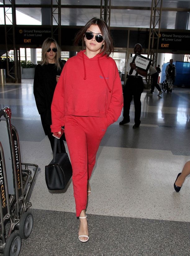 Selena Gomez pukeutui lennolleen rentoon oloasuun. Käsilaukku ja korot tuovat tyyliin ripauksen ylellisyyttä.