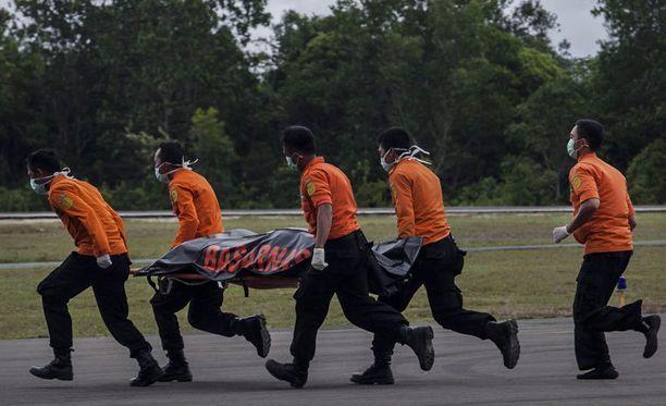 Pelastustyöntekijät kuljettavat merestä nostettua matkustajaa paareilla.